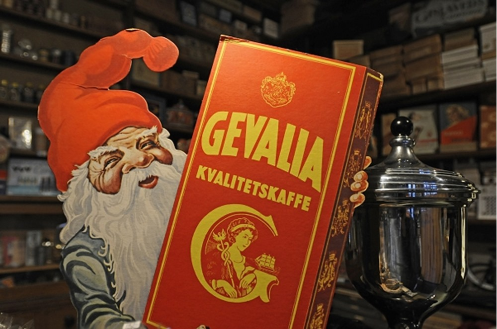 Santa Claus displaying commercial sign for coffee