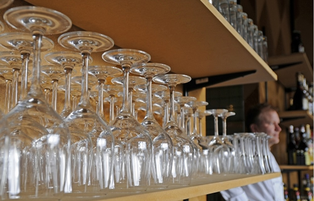 Glasses in a shelf with person in background