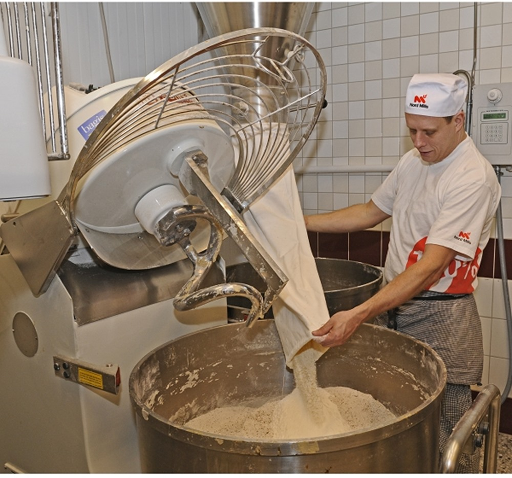 Woman applying doug in can in a bakery