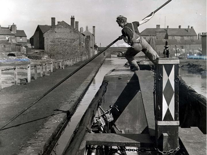 A worker pushes a barge away from dock with a long pole