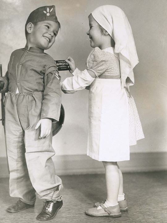 Two children posing as soldier and nurse