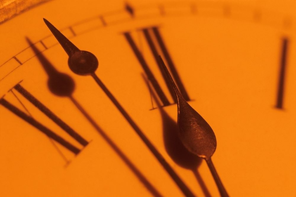 closeup of clock hands showing close to twelve