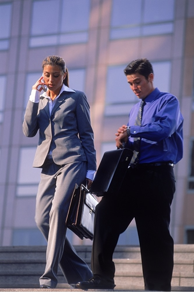 Business people on the move man looking at watch & woman on cellphone w,briefacases