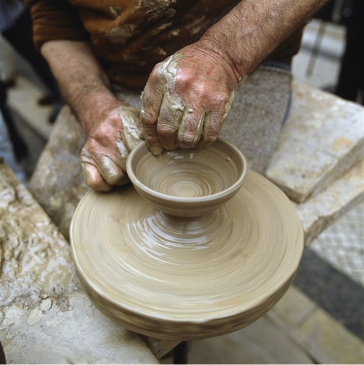 A potter sculpting a bowl on a pottery wheel