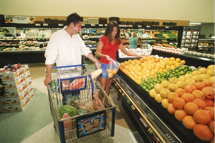 Couple pushing shopping cart through produce section of super market in USA