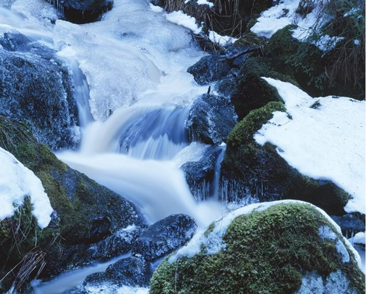 A view of waterfall in the rocks with snow