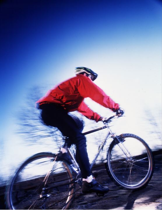 A cyclist in red jacket against a background of blue sky driving up the hill