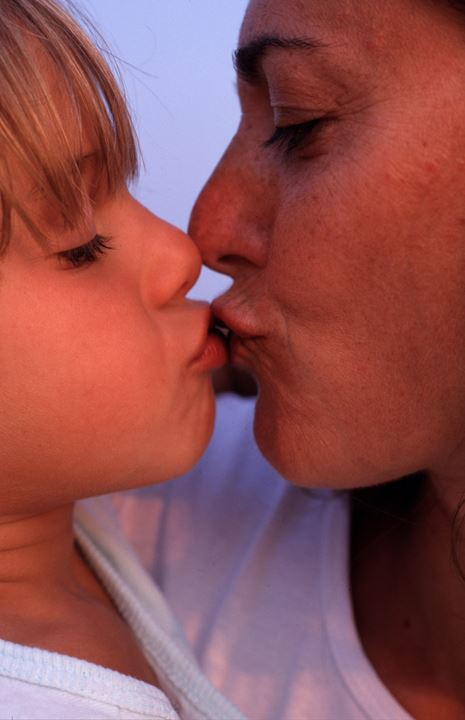 A mother kissing her child