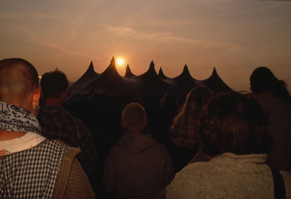 People looking at the setting sun over a tent