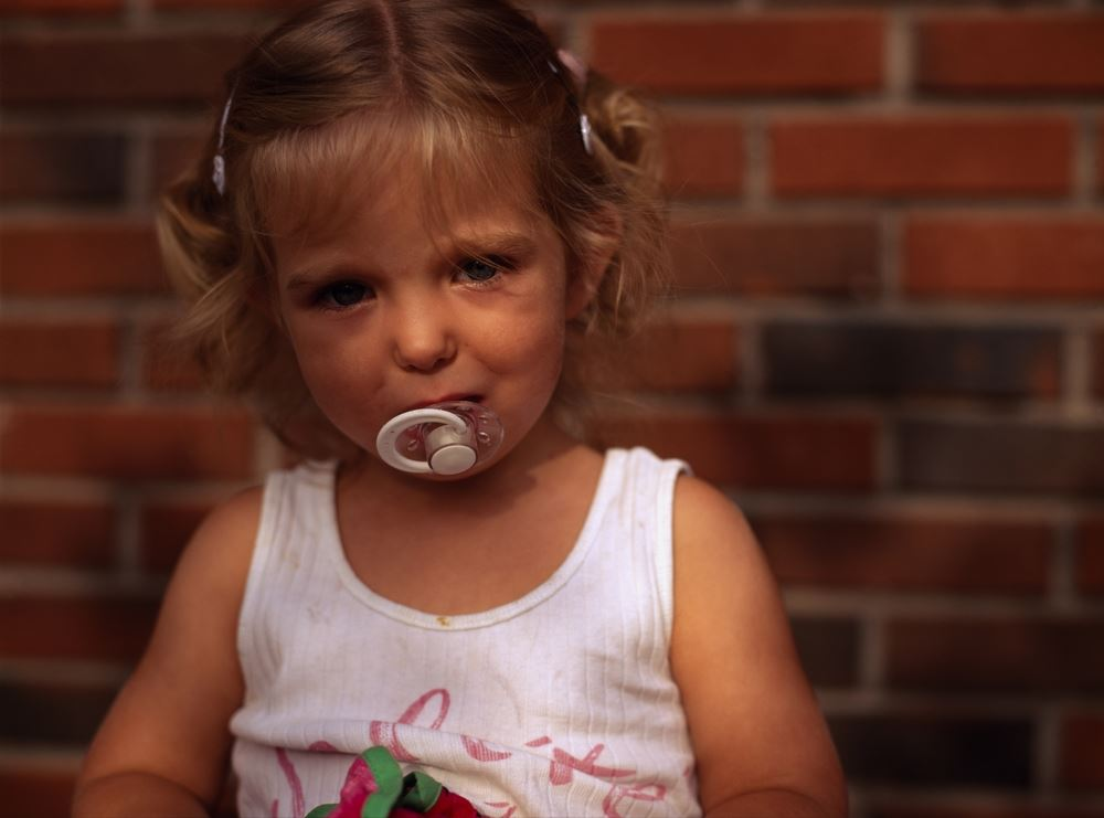 A little girl with a pacifier in her mouth