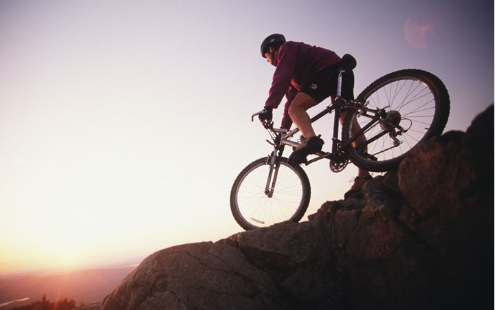 A cyclist on a mountain in evening sun rays