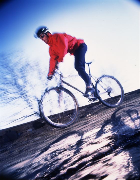 A cyclist in red jacket against a background of blue sky driving down the hill