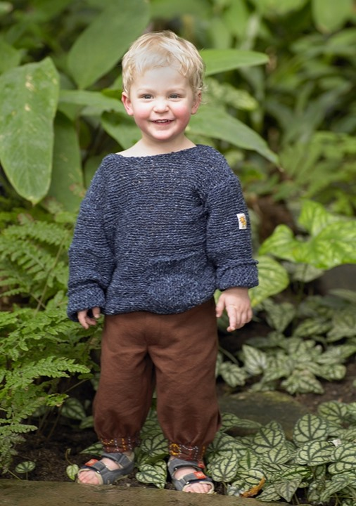 Smiling ruddy boy wearing sweater and sandals