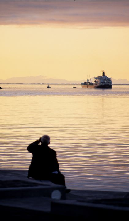 A man looking out to sea at a trawler nearby