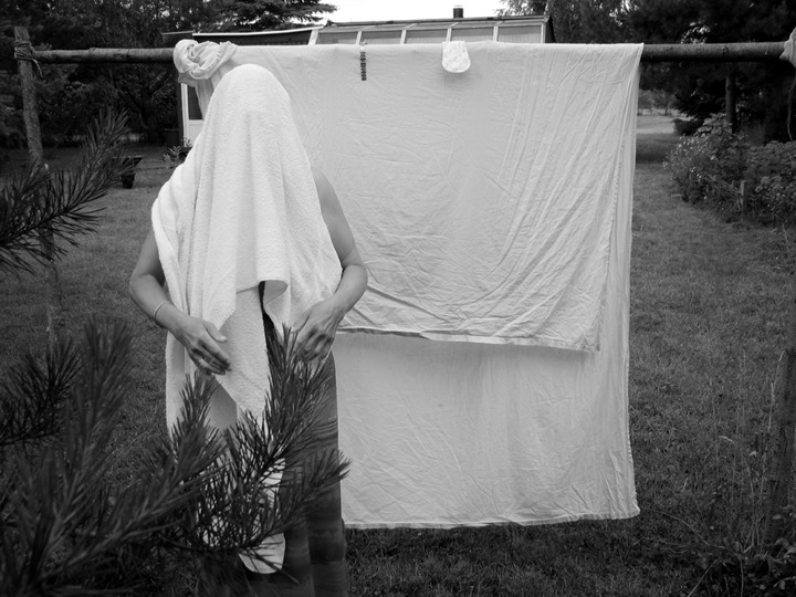 Person with a towel on head standing by drying laundry in the backyard