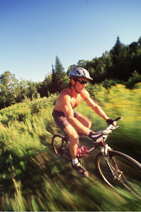 Nude cyclist driving through the grass