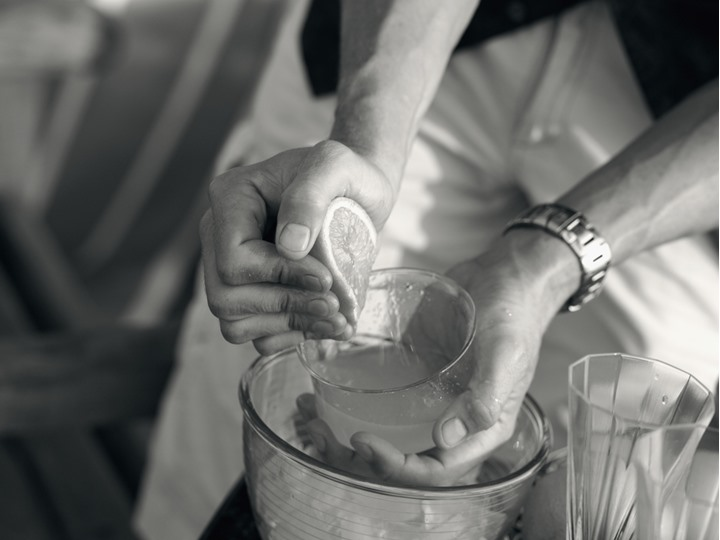 Hands of a man squeezing an orange