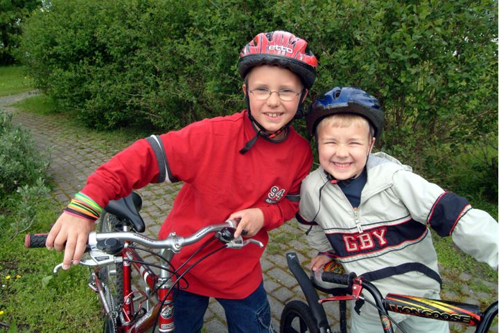 Two boys on their bikes, wearing helmets and smiling at camera