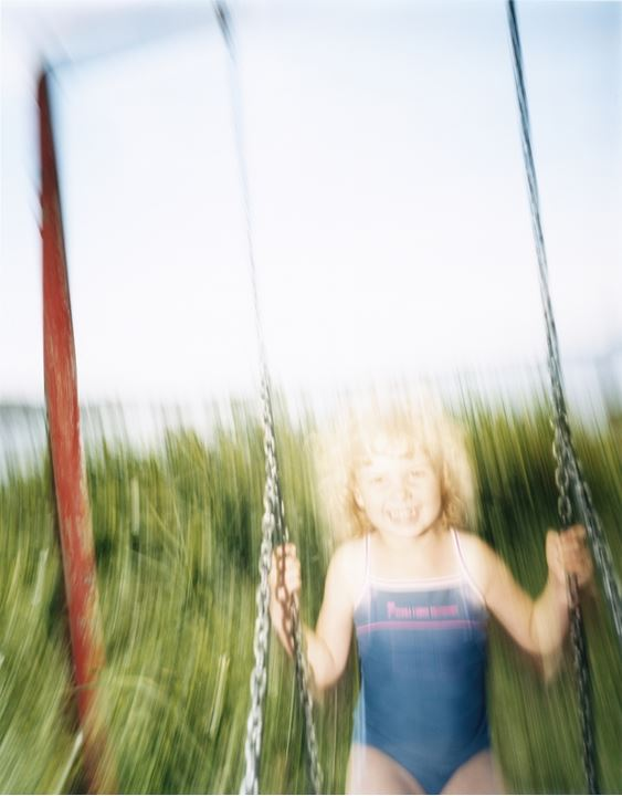 A smiling girl in a swing