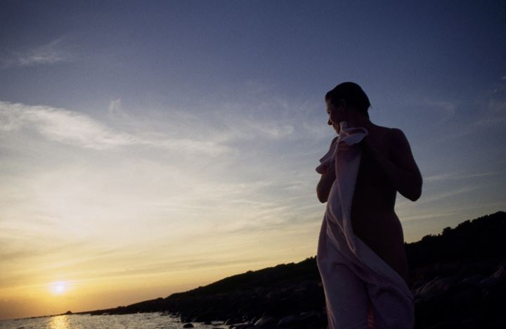 A woman drying herself with a towel by a lake at sunset