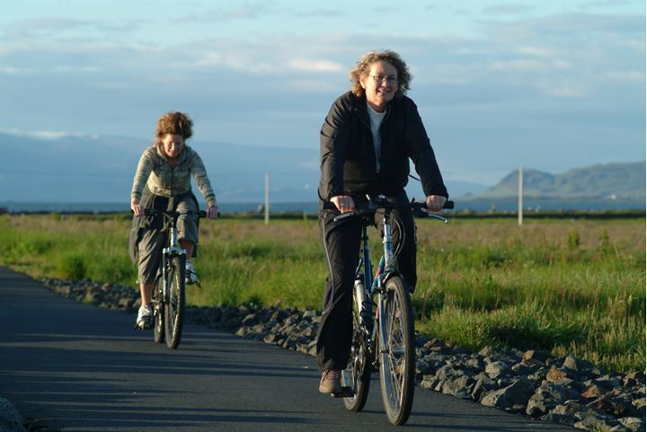 Two women riding bikes along a footpath, mountains in background