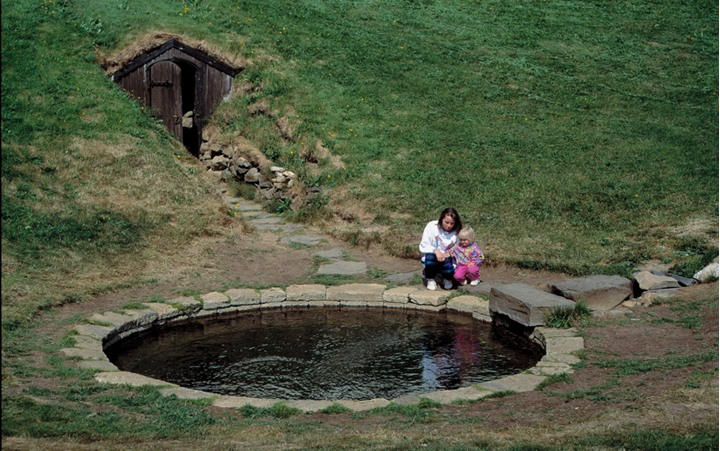 A woman and a little girl kneeling by an old, outdoors pool, believed to have been those of Snorri Sturluson